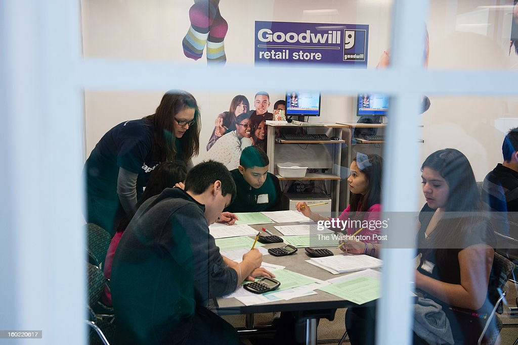 Students gather in the goodwill storefront to fill out paperwork. Eighth graders in Fairfax participate in a financial literacy program where they attend the Junior Achievement Financial Academy, run in partnership with Capital One Bank. At the academy, the students are given real-life exercises about mortgages, paying bills, applying for credit. On this day students from Holmes Middle School attend the academy.