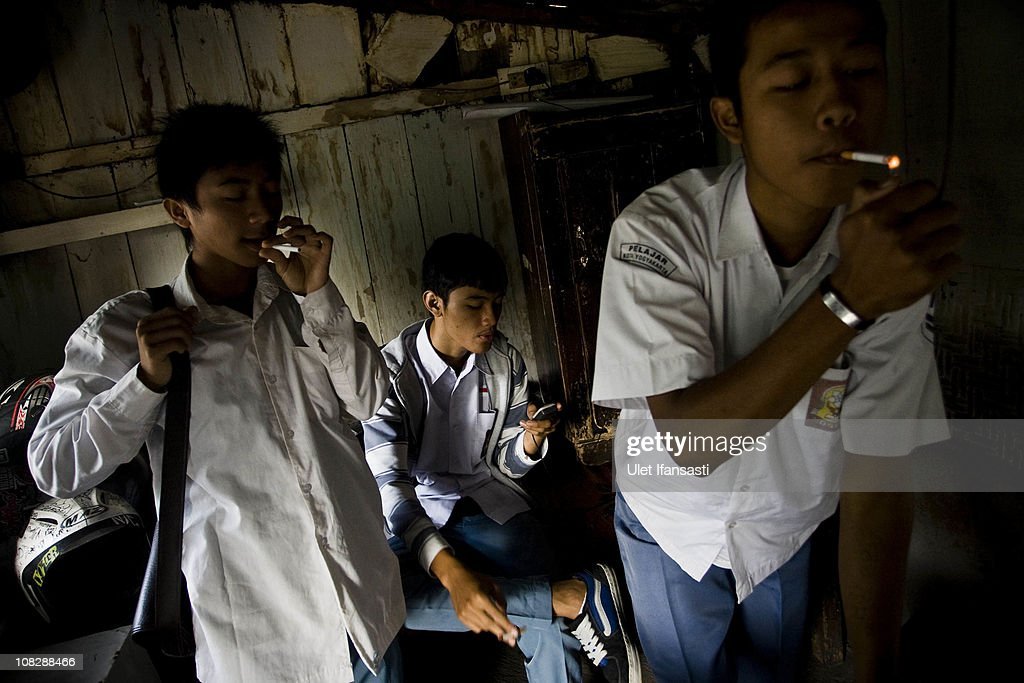 Students gather smokes at the stall before attending school on January 24, 2011 in Yogyakarta, Indonesia. It is estimated that over 25 percent of children in Indonesia over the age of three have tried smoking, with over three percent of them smoking regularly. The lack of government regulation around advertising is blamed for the problem, with campaigns seen heavily at sporting events, music concerts. The Indonesian government previously passed a health bill in 2009 to address the issues, but it has not yet been implemented.