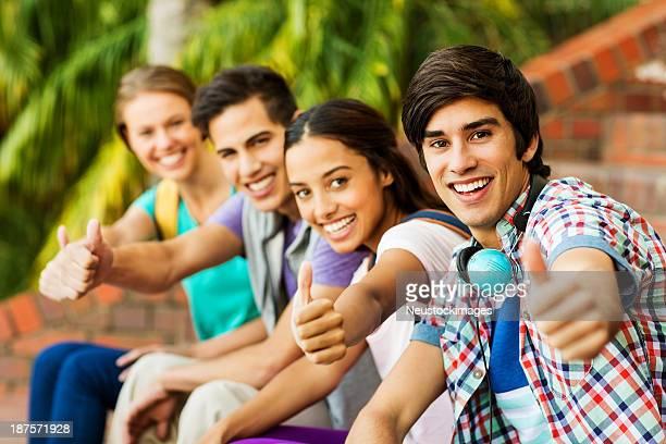 Studenten Gestikulieren Daumen hoch und sitzen auf College-Campus
