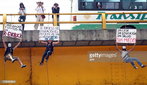 Students hang from a bridge during a protest against a reform on higher education in Cali Valle del Cauca department on October 12 2011 Thousands of...