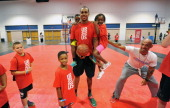 Students hang on Milwaukee Bucks forward John Henson at the John Henson Experience benefitting Up2Us at the Tampa Bay Youth Sports Expo on July 19...