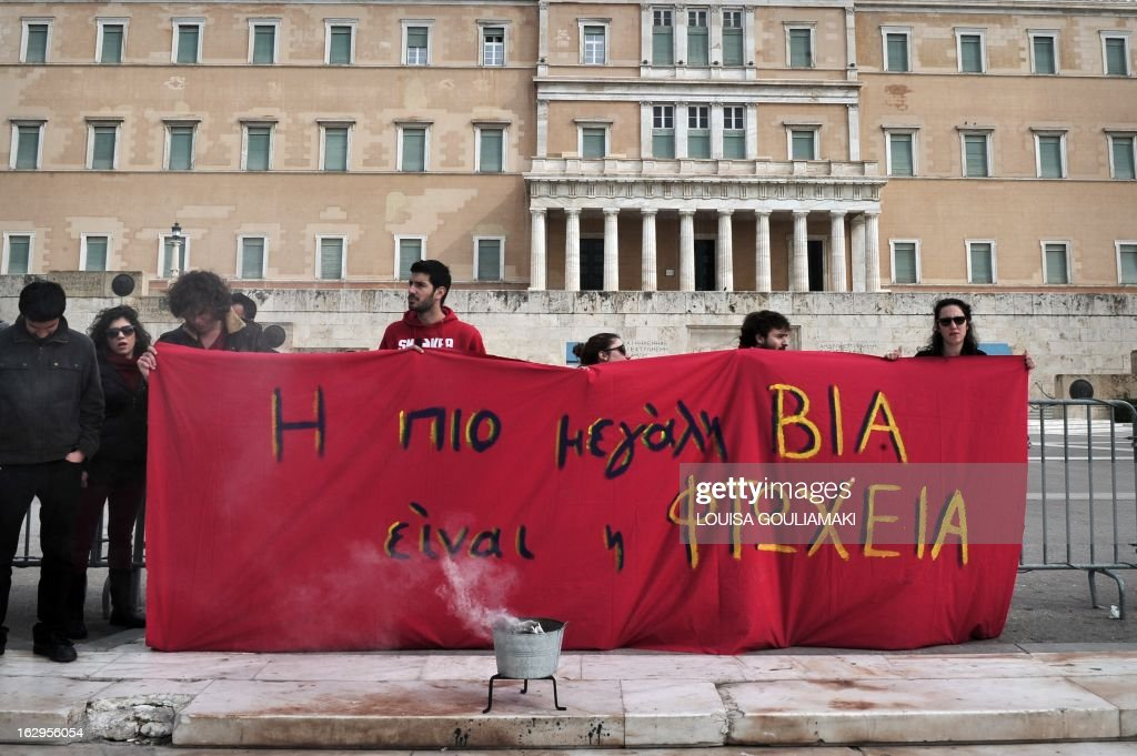Students hold a banner in front of the greek parliament in Athens, reading 'the biggest violence is the poverty', during a protest of Greek teachers and students on March 2, 2013 against cutbacks in the public education system due to the government's austerity measures. Demonstrators protested on March 2 lack of heat and food in many schools and the overall downgrade of the public education.