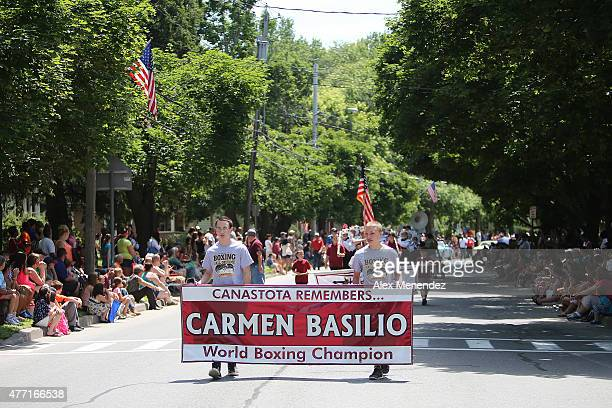 Students hold a banner in remembrance of past world boxing champion Carmen Basilio during the parade at the International Boxing Hall of Fame...