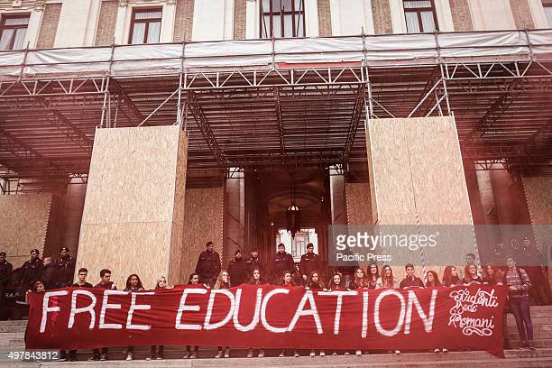 Students hold a banner reading 'Free education' at the Ministry of Education during a national demonstration to protest against Italian Prime...