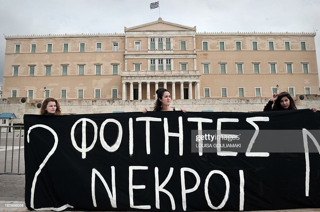 Students hold a black banner reading 'Two students dead' in front of the greek parliament in Athens, during a protest of Greek teachers and students on March 2, 2013 against cutbacks in the public education system due to the government's austerity measures. Demonstrators protested on March 2 lack of heat and food in many schools and the overall downgrade of the public education. AFP PHOTO / LOUISA GOULIAMAKI