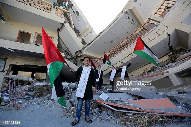 Students hold a Palestinian flag as they listen to Palestinian deputy minister of education Ziyad Sabid's speech on the first day of the new school...