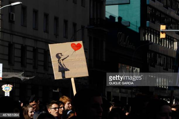 Students hold a placard with a Bansky design depicting an a girl with an air balloon and reading ' Education' during the second day of demonstration...