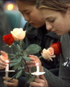 Students hold flowers and candles at prayer vigil for the victims at Columbine High School in Littleton Colo where two teenagers shot to death 12...