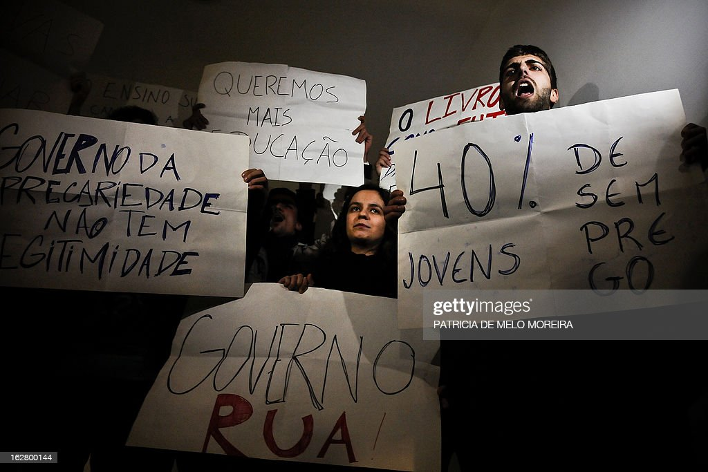 Students hold placards reading 'This Government of precariousness lacks legitimacy' (L), 'We want more education' (C-top), 'Youth unemployment 40 percent' (R) and 'Government Out' as they protest against government's austerity measures while Portugal's Prime Minister attends a conference at the Law University of Lisbon on February 27, 2013. Demonstrators gathered at the University today to protest against government's austerity measures imposed by the so-called Troika of public creditors -- the European Union, the European Central Bank and the International Monetary Fund. AFP PHOTO / PATRICIA DE MELO MOREIRA