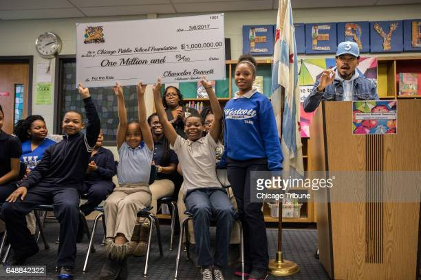 Students hold up a check for $1 million dollars from Chance the Rapper right who holds a press conference at Westcott Elementary School in Chicago's...