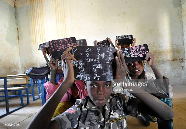 Students hold up thier chalk boards in a classroom whose majority of tables and benches were taken by Islamists on the first day of the reopening of...