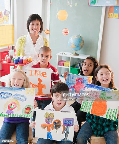 Students holding artwork with teacher