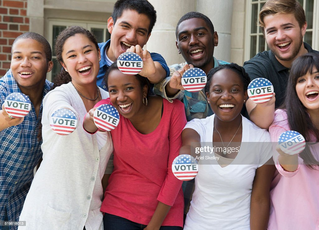 Students holding buttons at voter registration : Stock Photo