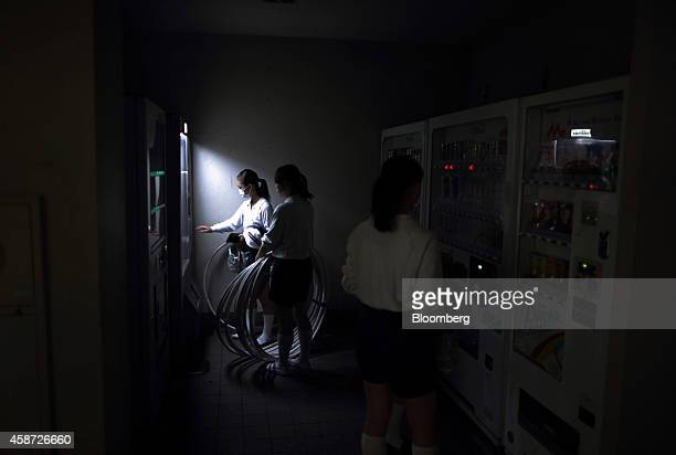 Students holding exercise hoops use a vending machine at the Korean High School in Tokyo Japan on Thursday Sept 25 2014 The school in Tokyos Kita...