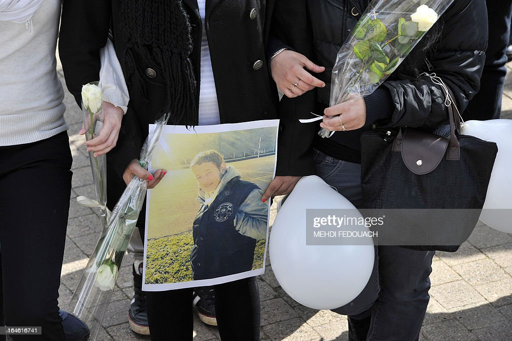 Students, holding flowers and a portrait, mourn on March 25, 2013 during a ceremony and march in honour of Sylvain (on the picture), a 15-year-old schoolboy stabbed on March 19 by a 19-year-old comrade in a classroom of the Estuaire college in Blaye, southwestern France.