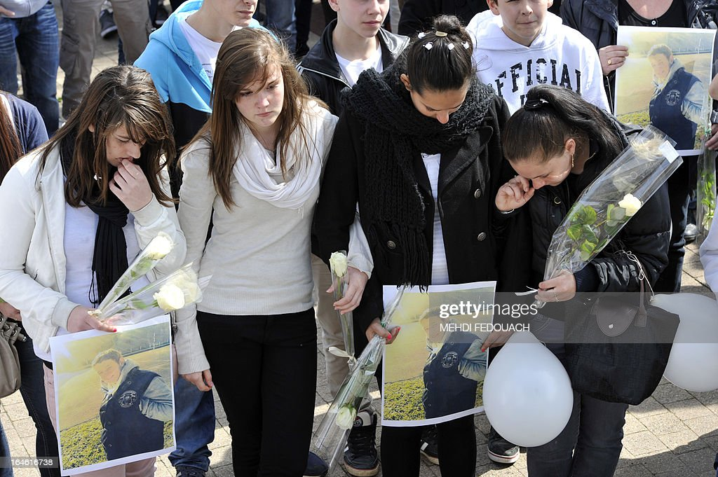 Students, holding flowers and portraits, mourn on March 25, 2013 during a ceremony and march in honour of Sylvain (on the pictures), a 15-year-old schoolboy stabbed on March 19 by a 19-year-old comrade in a classroom of the Estuaire college in Blaye, southwestern France.