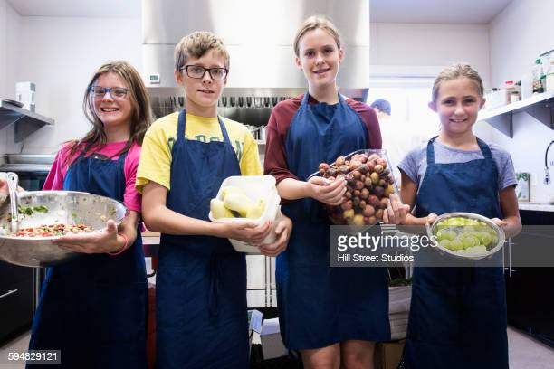 Students holding produce in cooking class