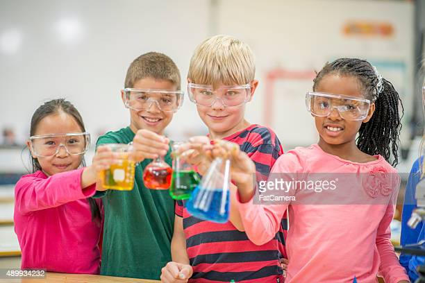 Students Holding Test Beakers with Primary Colors