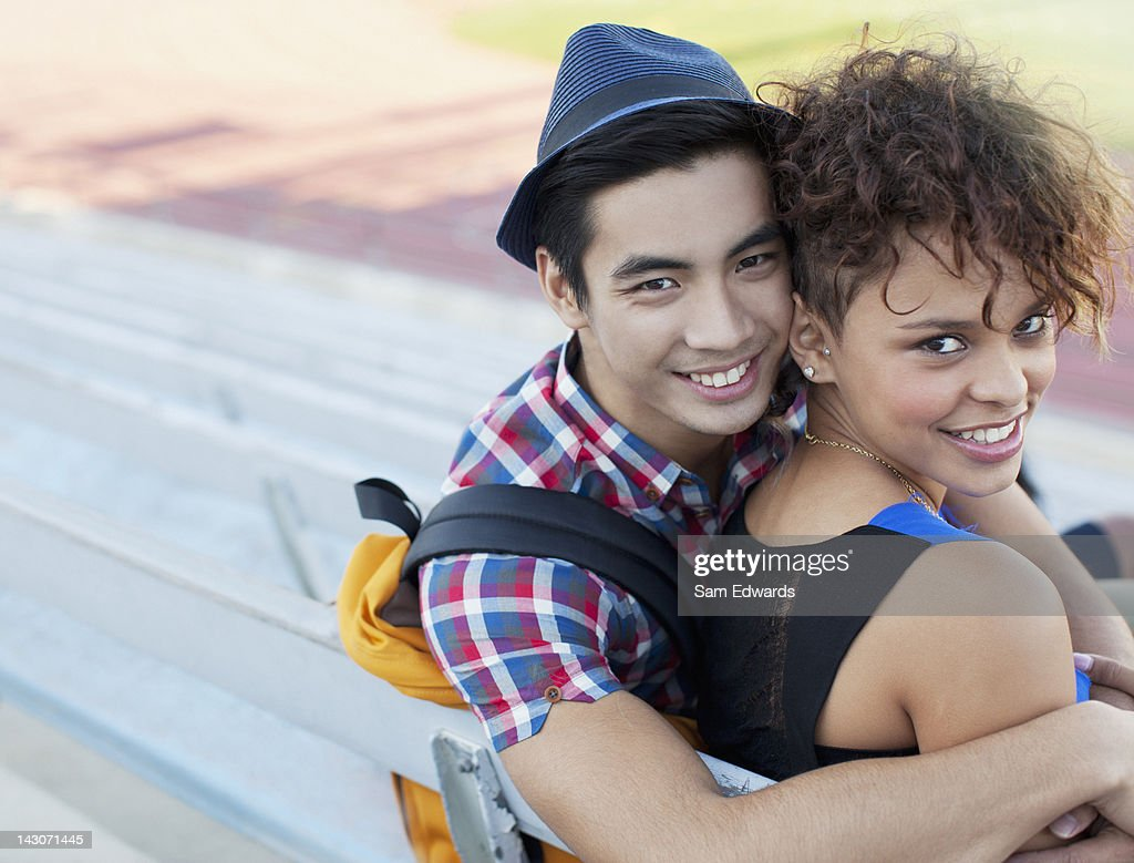 Students hugging on bleachers : Stock Photo