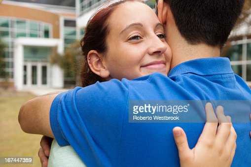 Students hugging on campus : Stock Photo