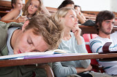 Students in a classroom with one sleeping