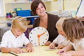 Students in class learning how to tell time (selective focus)