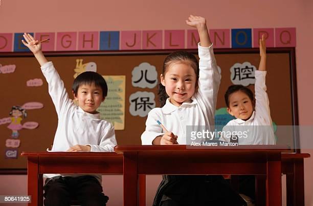 Students in class raising hands