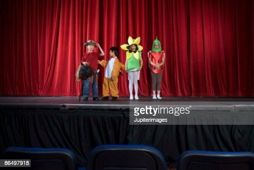 Students in costumes on stage : Stock Photo