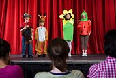Students in costumes on stage