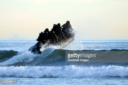 Students in Navy SEALs qualification training navigate the surf off the cost of Coronado. : Stock Photo