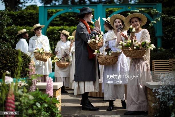 Students in period costume perform as flower sellers in the Sir Simon Milton Foundation garden the Chelsea Flower Show on May 22 2017 in London...