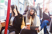 Two young university student in public transport have a fun and using digital tablet and headphones