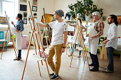 Group of creative students painting in workshop