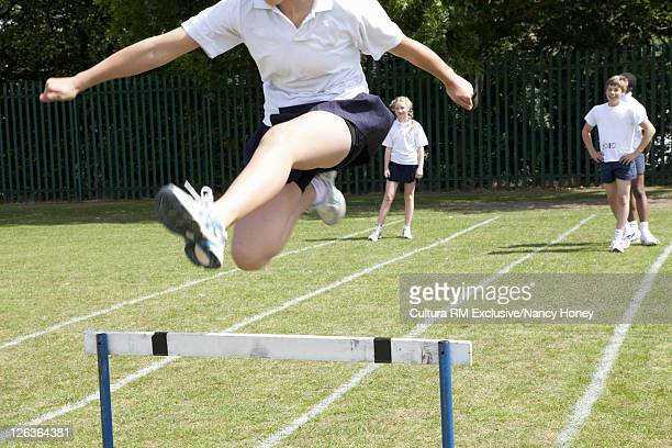Students jumping hurdles in P.E. class