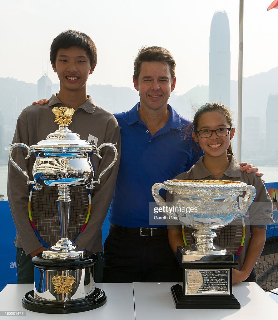 Students, Justin Chaung (17) and Kimbeley Lai (16) from King George the V, ESF School, pose for photos with Todd Woodbridge and the AO trophys, over looking the Hong Kong skyline, during the Australian Open Trophy tour on October 22, 2013 in Hong Kong, Hong Kong.