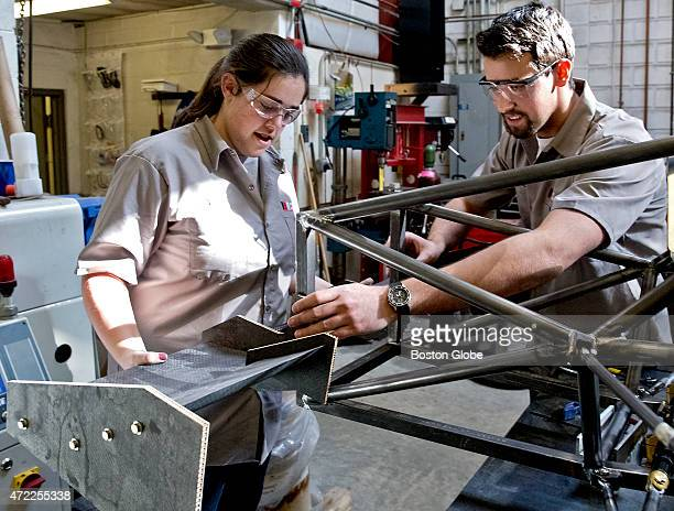 MIT students Kelly O'Brien aerodynamics lead and Orlando Ward team captain work on a carbon fiber wing on their team's electric formula SAE racecar...