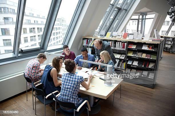 Estudiantes con el profesor de aprendizaje juntos en una biblioteca