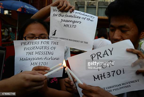 Students light candles as they hold placards in solidarity with families of the passengers of the missing Malaysia Airlines flight MH370 plane during...