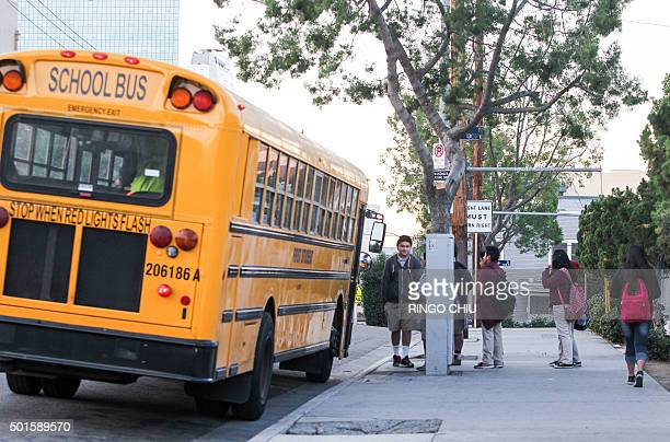 Students line up for a school bus outside a school in Los Angeles on December 16 2015 Responding to a threat emailed to school board members all Los...