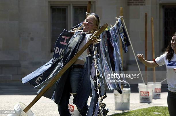 UCLA students Lisa White and Ann Caldwell catch a windblown closthesline of blue jeans with messages challenging misconceptions about sexual violence...
