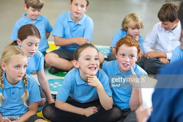 Students Listen To Teacher Reading to Class
