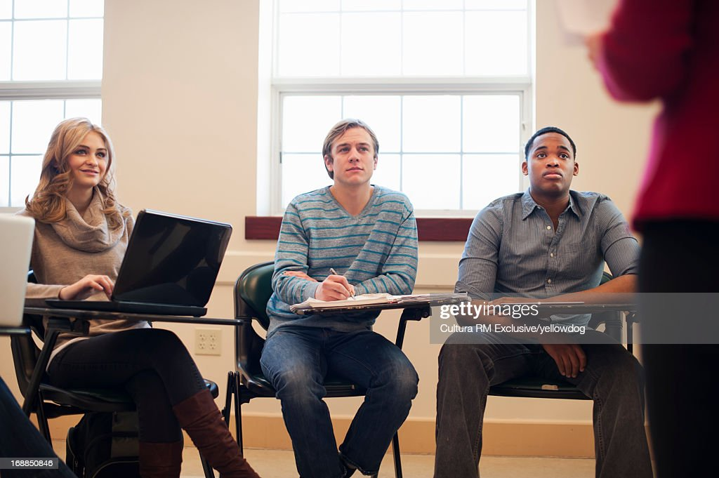 Students listening to teacher in class : Stock Photo