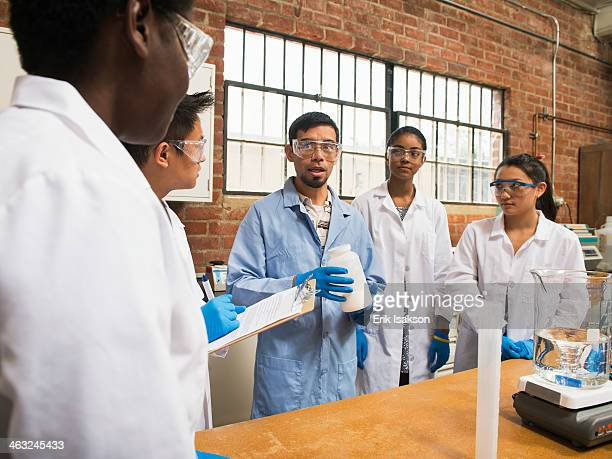 Students listening to teacher in science lab