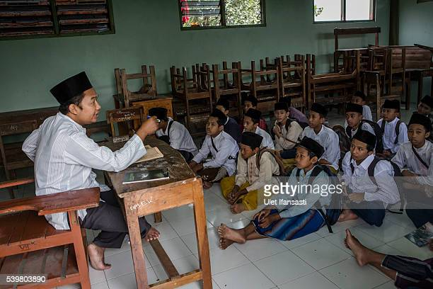 Students listening to their teacher as they study at the islamic boarding school Lirboyo during the holy month of Ramadan on June 9 2016 in Kediri...