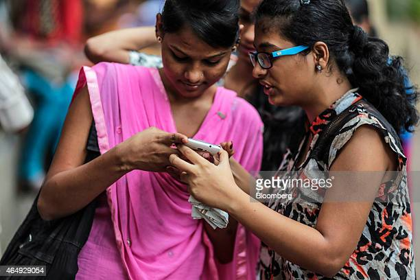 Students look at a Micromax Informatics Ltd smartphone in Mumbai India on Saturday Feb 28 2015 The government auction of telecom wireless spectrum...