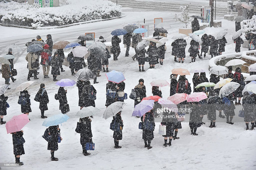 Students make lines on a bus terminal covered by snow to wait for transportation in Nagano City in the morning on December 10, 2012. Heavy snow hit wide areas of Japan on December 10 due to cold air that brought a winter pressure system.