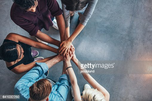 Students making a stack of hands : Stock Photo
