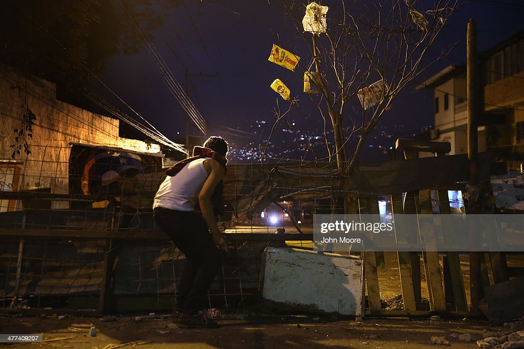 Students man a barricade in downtown while watching for Venezuelan security forces before dawn on March 9, 2014 in San Cristobal, the capital of Tachira state, Venezuela. Local residents have manned barricades throughout the nights for almost a month, protesting against the federal government. Tachira, which borders Colombia, has been a focal point for anti-government protests nationwide.