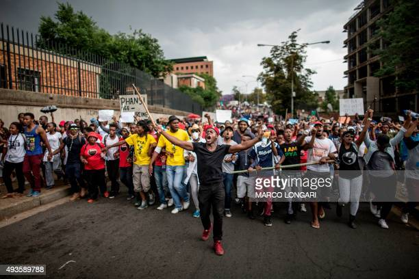 Students march through the campus of the University of the Witwatersrand in Johannesburg on October 21 during a protest against fee hikes...