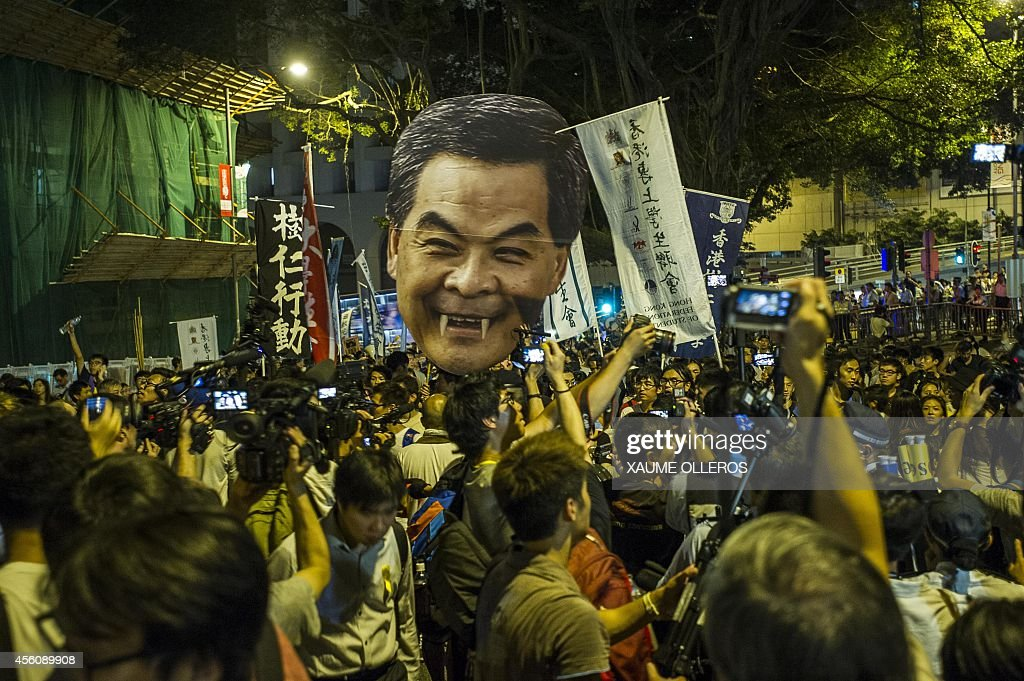 Students march to the Government House in Hong Kong holding a portrait of Chief Executive Leung Chun Ying on September 25 2014 to push him to...